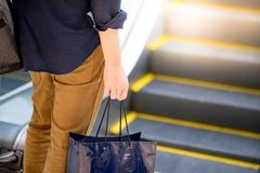 Male hand holding blue shopping bag in department store. Male hand holding blue shopping bag near escalator in department store. urban lifestyle in shopping mall Stock Photo