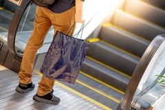 Male hand holding blue shopping bag in department store. Male hand holding blue shopping bag near escalator in department store. urban lifestyle in shopping mall Royalty Free Stock Image