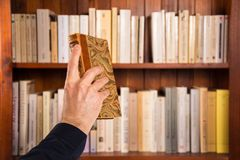 Male hand holding a book in front of bookshelves Stock Image
