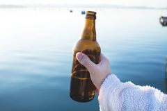 Male hand holding a bottle of beer on the background of the lake. royalty free stock images