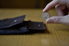 Male hand holding a bronze coin of ten Yens Japanese Yen, JPY and withdrawing that from the leather wallet Stock Images