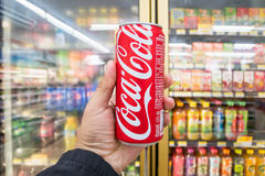 Male hand holding a can of Coca Cola in convenience store. stock images