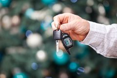 Male hand holding car key on Christmas background Stock Images