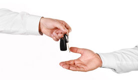 Male hand holding a car key and handing it over to another perso Royalty Free Stock Image