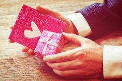 Male hand holding card and gift Stock Image