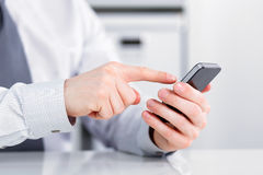Male hand holding a cell phone and writing Stock Image