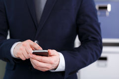 Male hand holding a cell phone and writing. Businessman holding a cell phone and writing sms message in office Royalty Free Stock Photo