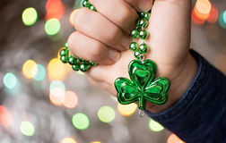 Male hand holding clover green necklace Stock Photos
