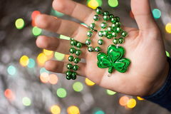 Male hand holding clover green necklace Royalty Free Stock Image