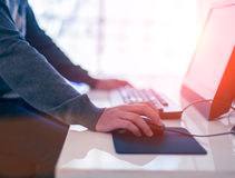 Male hand holding computer mouse with laptop keyboard Royalty Free Stock Image