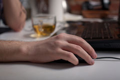 Male hand holding computer mouse with laptop keyboard in the background.  Stock Photos