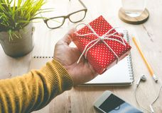 Male hand holding cute gift box presents on worktable. Background.For christmas,new year,birthday and happiness concepts ideas Stock Photography