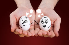 Male hand holding eggs with smiley faces Royalty Free Stock Images