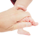 Male hand holding firmly around a foot of toddler in air Royalty Free Stock Images