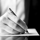 Male hand holding a fountain pen as though writing stock image