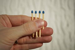 Male hand holding four safety match sticks hidden in the palm with one match stick shorter than the others Royalty Free Stock Image