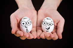 Male hand holding funny eggs Royalty Free Stock Photo