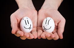 Male hand holding funny eggs Stock Images