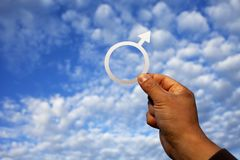 Male hand holding a gender symbol for men on the background of blue sky with clouds. Gender equity concept stock image