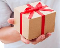 Male hand holding gift with ribbon. Stock Image