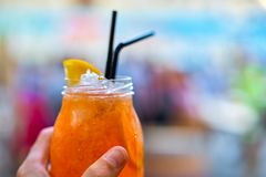 Male hand holding glass with spirits Spritz Aperol, on a blurred royalty free stock images