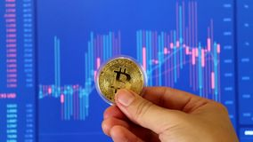 Male hand holding gold bitcoin coin on unfocused BTC/USD chart background