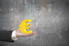Male hand holding golden euro sign. With business concepts doodles concrete wall background Stock Images