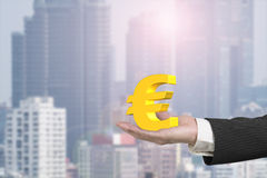 Male hand holding golden euro sign Stock Photos