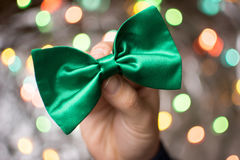 Male hand holding a green bow tie. Royalty Free Stock Photo