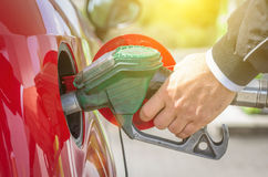 Male hand holding green pump filling gasoline Royalty Free Stock Photos