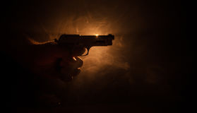 Male hand holding gun on black background with smoke ( yellow orange red white ) colored back lights, Mafia killer concept Royalty Free Stock Images