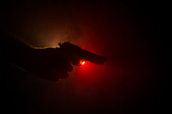 Male hand holding gun on black background with smoke ( yellow orange red white ) colored back lights, Mafia killer concept Stock Photo