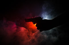 Male hand holding gun on black background with smoke ( yellow orange red white ) colored back lights, Mafia killer concept. Male hand holding gun on black stock image