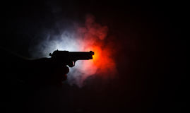 Male hand holding gun on black background with smoke ( yellow orange red white ) colored back lights, Mafia killer concept Royalty Free Stock Photo
