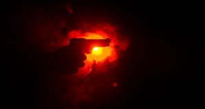 Male hand holding gun on black background with smoke ( yellow orange red white ) colored back lights, Mafia killer concept Stock Image