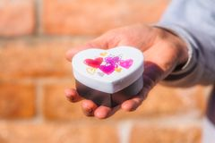 Male hand holding heart shaped gift box Stock Photo