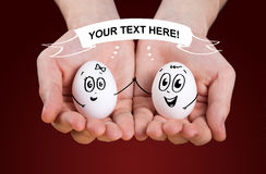 Male hand holding holding eggs with smiley faces Royalty Free Stock Photos
