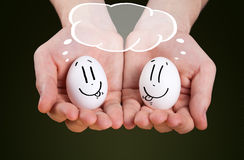 Male hand holding holding eggs with smiley faces Stock Photos