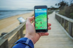 Male hand holding iPhone 6 with Pokemon Go on boardwalk Stock Image