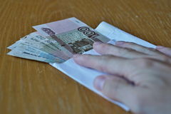 Male hand holding its fingers on Russian currency Russian Rubles on the wooden table Royalty Free Stock Image