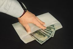 Male hand holding its fingers on white envelope full of American Dollars. USD, US Dollars, on the wooden table as a symbol of illegal cash transfer or bribery Royalty Free Stock Image
