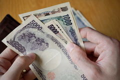 Male hand holding Japanese currency (yen) with its Asian symbols in the form bank notes and withdrawing them from wallet. Male hand holding Japanese currency ( Stock Photos