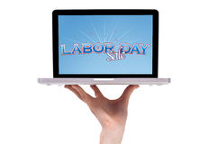 A male hand holding a laptop with a labor day sign royalty free stock photography