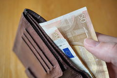 Male hand holding a leather wallet and withdrawing European currency (Euro, EUR) Royalty Free Stock Image
