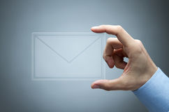 Male hand holding mail icon. Human hand holding futuristic transparent mail icon Royalty Free Stock Photos
