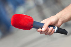 Male hand holding microphone Stock Images