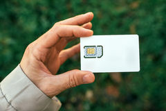 Male hand holding mobile phone SIM card Stock Photos