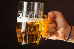 Male hand holding mug of beer Stock Photos