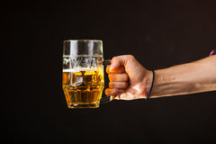 Male hand holding mug of beer Royalty Free Stock Images