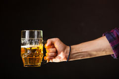 Male hand holding mug of beer Royalty Free Stock Photo